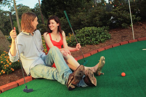 Happy young couple on a miniature golf date.