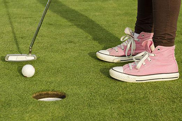 Golfer in converse shoes putting