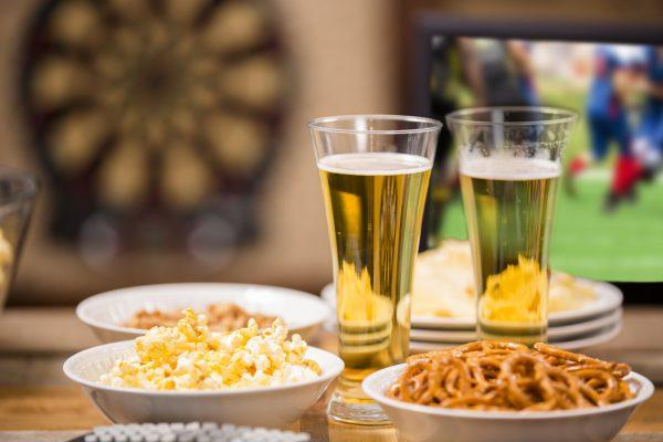 Sports bar. Popcorn, pretzels, beer, dartboard. Football game on TV.