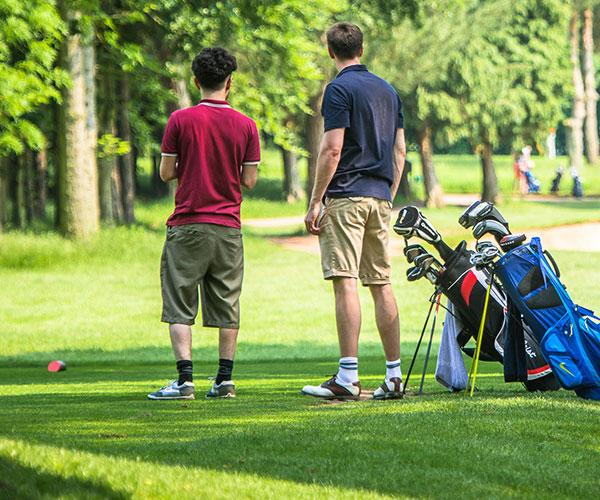 Two men with golf bags on the course