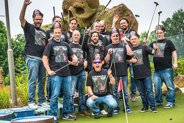 Large group in matching t-shirts playing adventure golf
